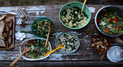 potluck salads on aged wooden table