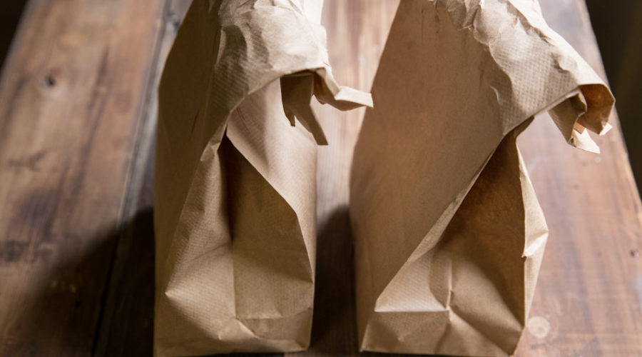 Two brown paper lunch bags on wooden table.