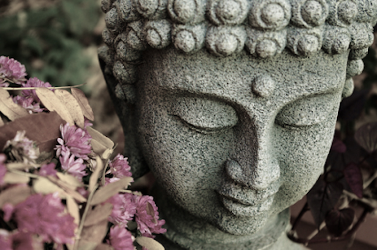 A bowed head of Buddha, with dried flowers nearby