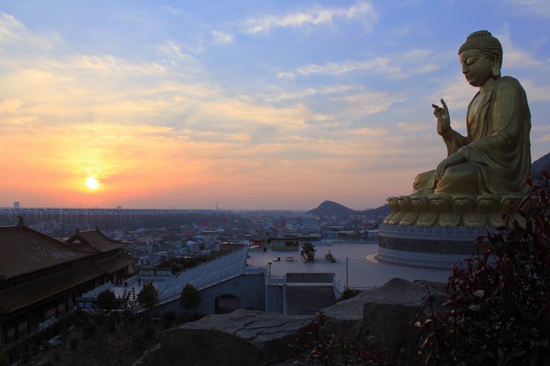 Buddha above the city at sunset