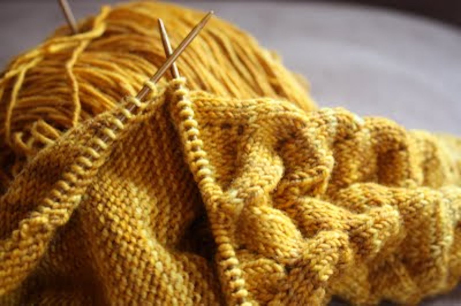 deep gold yarn with knitting needles