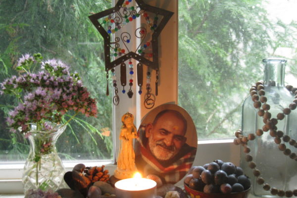 Windowsill altar with candle, berries, and Maharaji