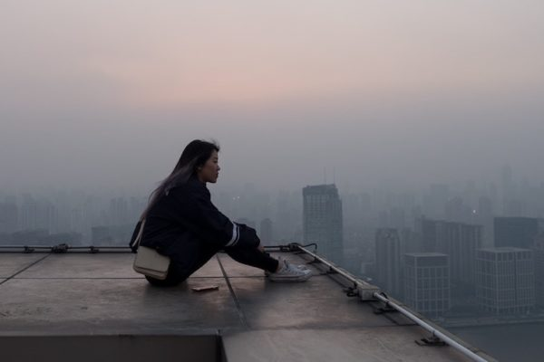 woman gazing at city from rooftop